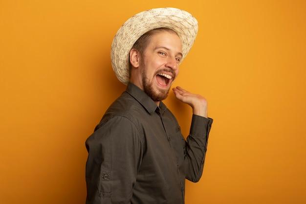 Młody przystojny mężczyzna w szarej koszuli i letnim kapeluszu szczęśliwy i podekscytowany gestykuluje ręką