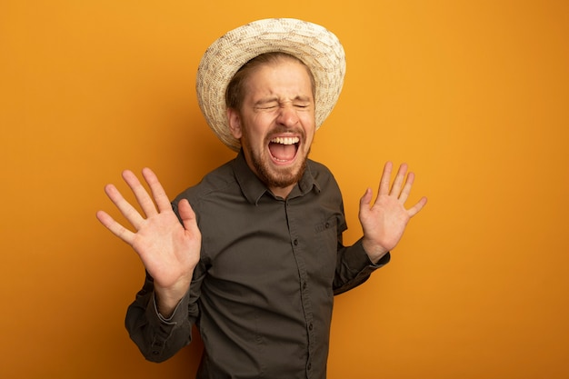 Młody przystojny mężczyzna w szarej koszuli i letnim kapeluszu szczęśliwy i podekscytowany śmiejąc się z podniesionymi rękami