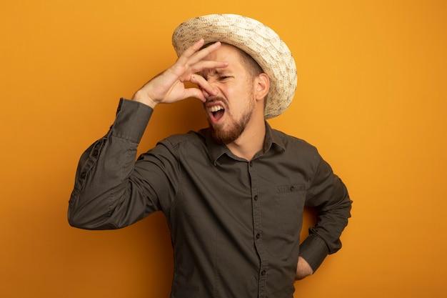 Młody przystojny mężczyzna w szarej koszuli i letnim kapeluszu zakrywającym nos palcami cierpiącymi na smród