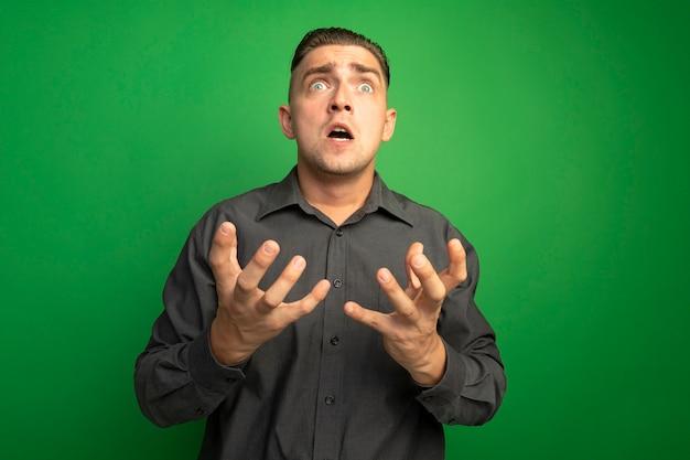 Młody przystojny mężczyzna w szarej koszuli krzyczy z wyciągniętymi rękami, szalony i sfrustrowany, stojąc nad zieloną ścianą