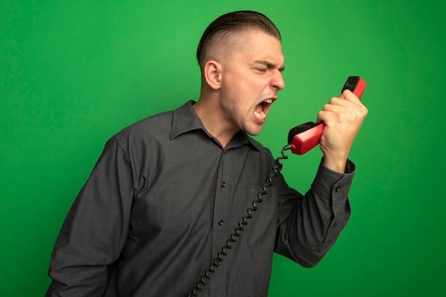 Młody przystojny mężczyzna w szarej koszuli rozmawia przez telefon rocznika krzyczy i wrzeszczy sfrustrowany