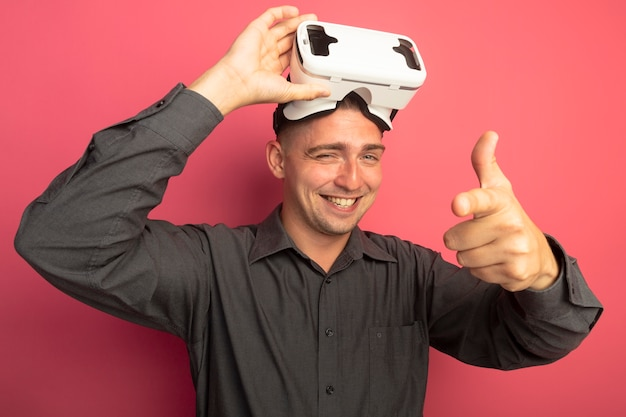 Młody przystojny mężczyzna w szarej koszuli w okularach wirtualnej rzeczywistości, patrząc na przód, uśmiechnięty, mrugający, pokazujący kciuki stojąc nad różową ścianą
