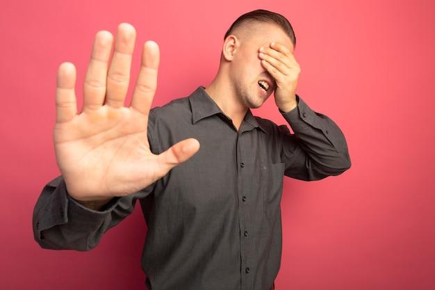 Młody przystojny mężczyzna w szarej koszuli wygląda zmęczony i znudzony robi gest stop z otwartą ręką stojąc na różowej ścianie