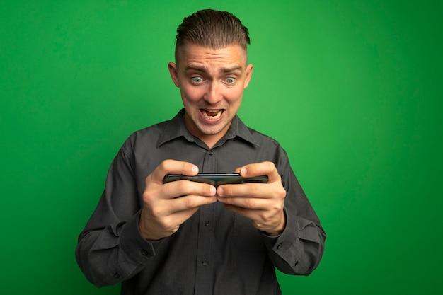 Młody przystojny mężczyzna w szarej koszuli za pomocą smartfona grając w gry podekscytowany i emocjonalny stojąc nad zieloną ścianą