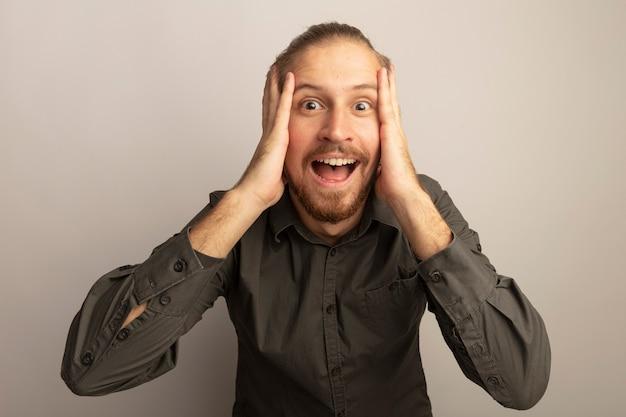Młody przystojny mężczyzna w szarej koszuli zdumiony i zaskoczony z rękami na twarzy