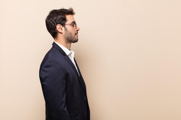 Młody przystojny mężczyzna w widoku profilu, który chce skopiować przestrzeń do przodu, myśląc, wyobrażając sobie lub marząc na jawie