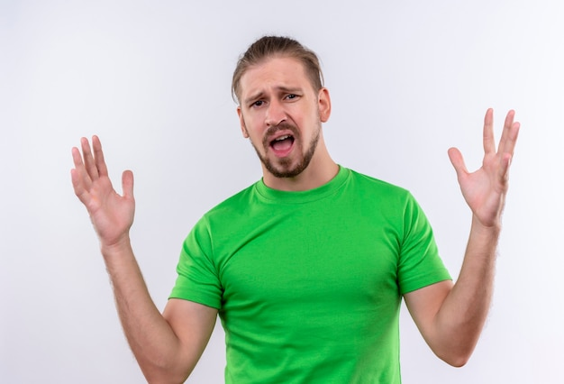 Młody przystojny mężczyzna w zielonej koszulce patrząc na kamery rozczarowany z podniesionymi rękami stojącymi na białym tle