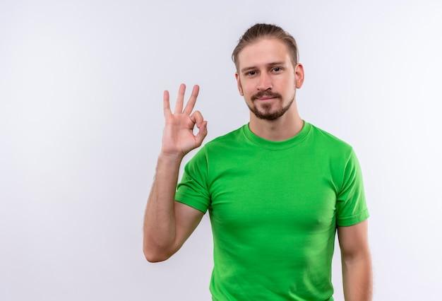 Młody przystojny mężczyzna w zielonej koszulce patrząc na kamery, uśmiechając się czysto robi ok znak stojąc na białym tle