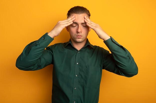 Młody przystojny mężczyzna w zielonej koszuli dotyka jego głowy zmęczony i znudzony ból głowy