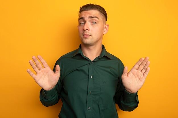 Młody przystojny mężczyzna w zielonej koszuli mylić, nie mając odpowiedzi, podnosząc ręce
