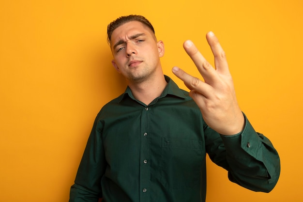 Młody przystojny mężczyzna w zielonej koszuli pokazuje i wskazuje palcem numer trzy patrząc pewnie