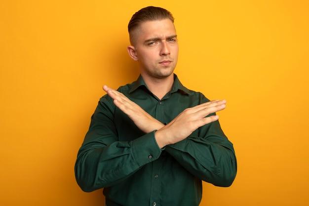 Młody przystojny mężczyzna w zielonej koszuli robi gest sto skrzyżowania ramion z poważną twarzą