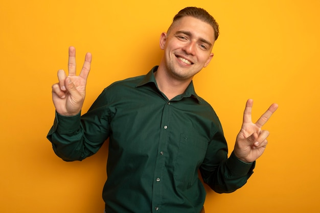 Młody przystojny mężczyzna w zielonej koszuli uśmiechnięty radośnie pokazując znak v obiema rękami