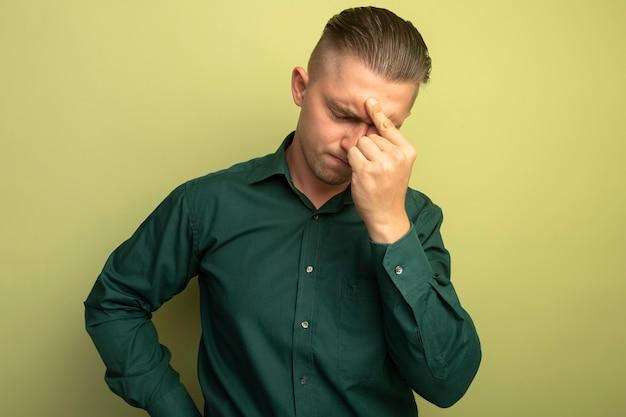 Młody przystojny mężczyzna w zielonej koszuli wygląda na zmęczonego i znudzonego dotykając jego nosa między zamkniętymi oczami