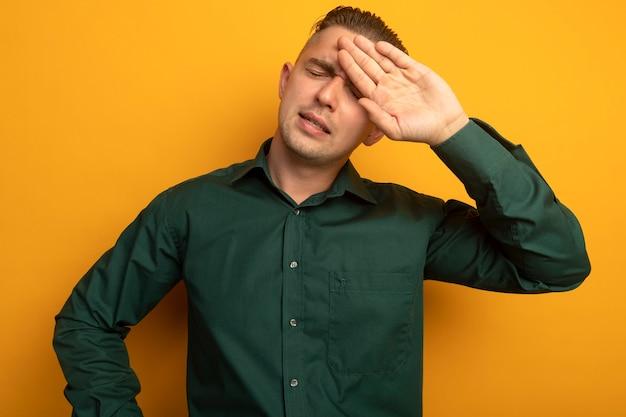 Młody przystojny mężczyzna w zielonej koszuli, zmęczony i znudzony, stojąc na pomarańczowej ścianie z ręką na czole