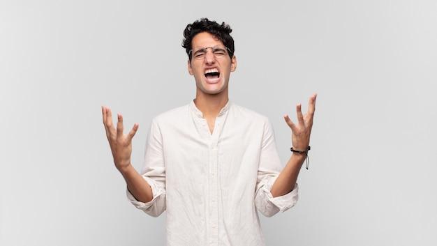 Młody przystojny mężczyzna wściekle krzyczy, czuje się zestresowany i zirytowany z rękami uniesionymi do góry, mówiąc dlaczego ja