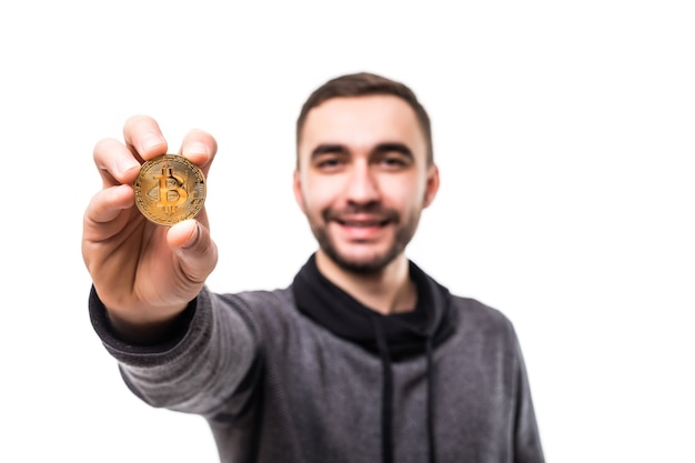 Młody przystojny mężczyzna wskazał złotego bitcoina na aparat na białym tle