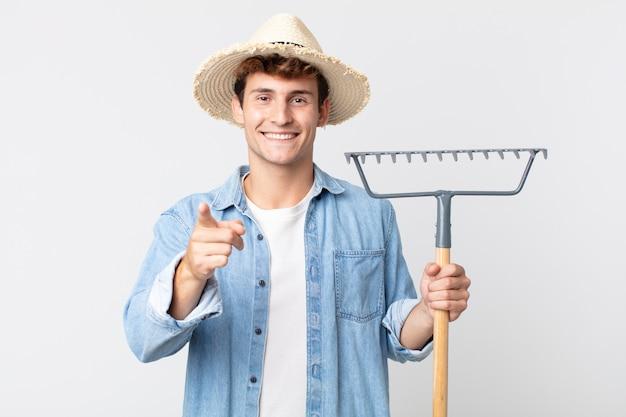 Młody przystojny mężczyzna, wskazując na aparat wybierając ciebie. koncepcja rolnika