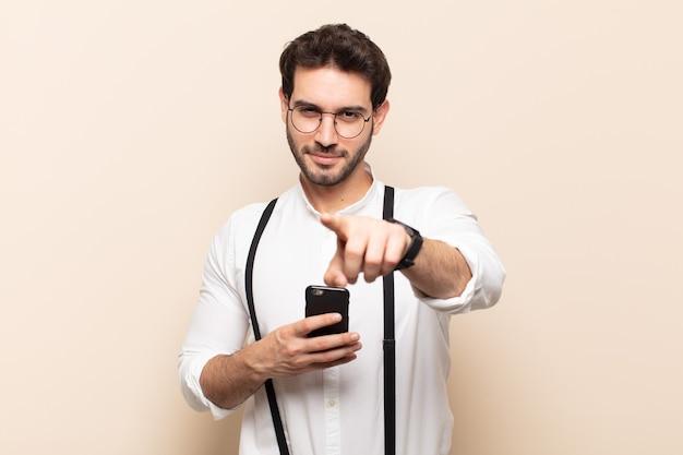 Młody przystojny mężczyzna, wskazując na aparat z zadowolonym, pewnym siebie, przyjaznym uśmiechem, wybiera cię