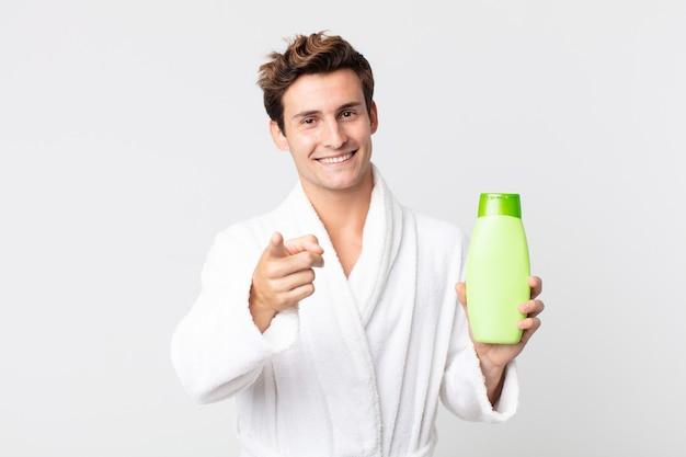 Młody przystojny mężczyzna wskazujący na aparat fotograficzny wybierający cię w szlafroku i trzymający butelkę szamponu