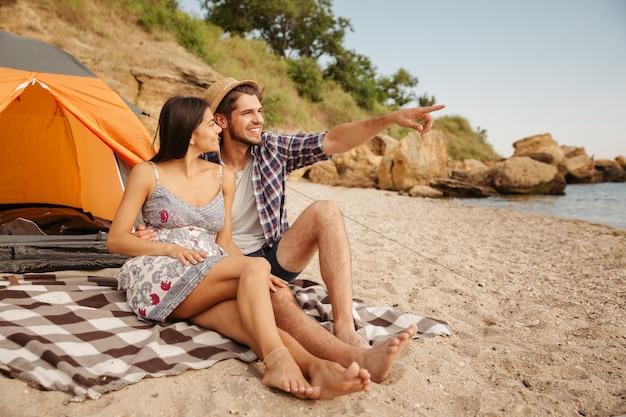 Młody przystojny mężczyzna wskazujący na coś siedzącego z dziewczyną w namiocie na plaży