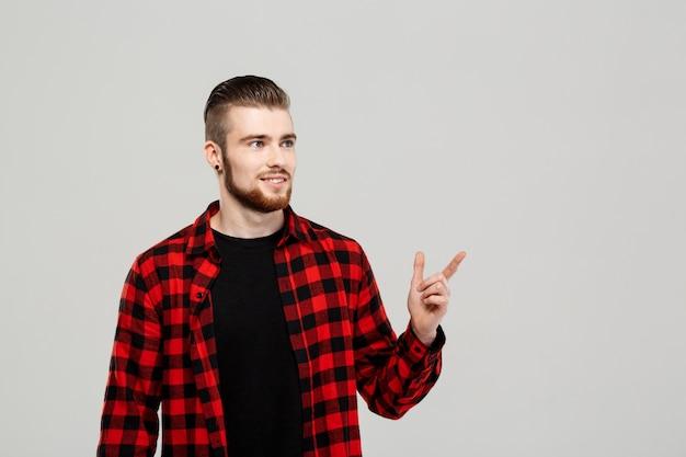 Młody przystojny mężczyzna wskazuje palec w stronie nad szarości ścianą.