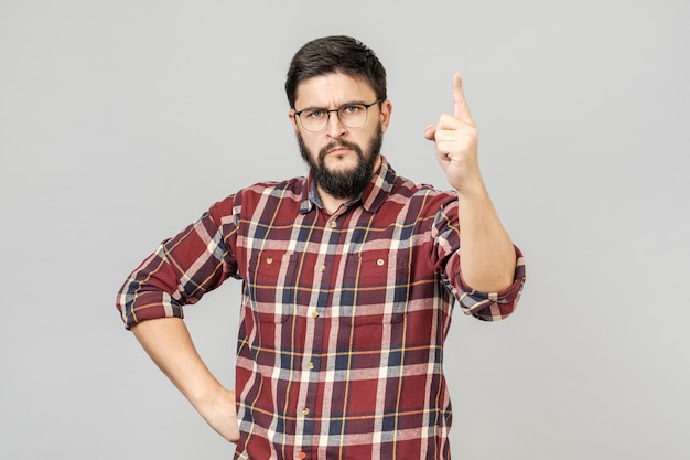 Młody przystojny mężczyzna wskazuje z palcem up nad odosobnionym szarym tłem