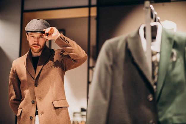 Młody przystojny mężczyzna wybiera kapelusz przy sklepem