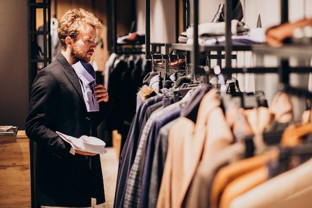 Młody przystojny mężczyzna wybiera koszula przy sklepem