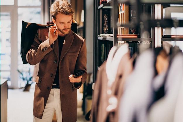 Młody przystojny mężczyzna wybiera płótno przy sklepem