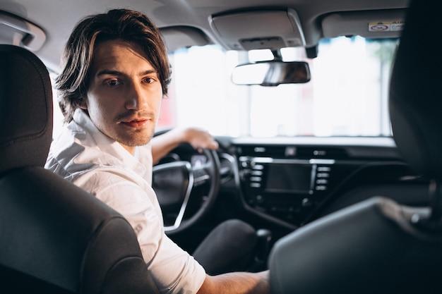 Młody przystojny mężczyzna wybiera samochód w samochodowej sala wystawowej