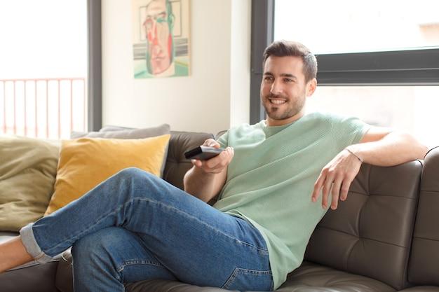 Młody przystojny mężczyzna wybierający kanał telewizyjny