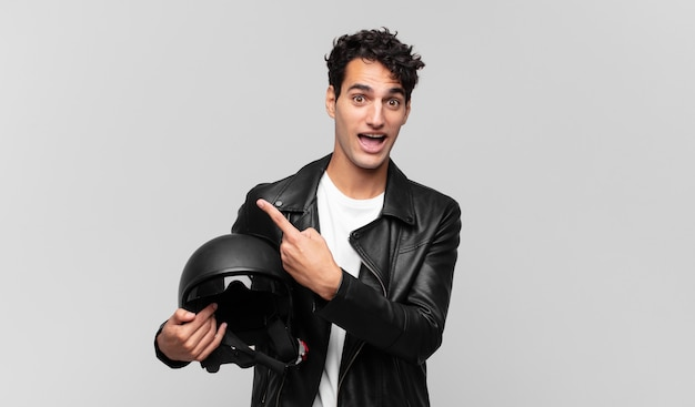Młody przystojny mężczyzna wygląda podekscytowany i zaskoczony, wskazując na bok i do góry, aby skopiować miejsce. koncepcja motocyklisty