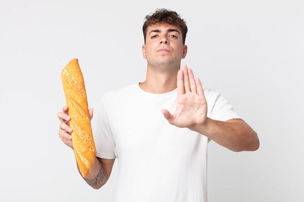 Młody przystojny mężczyzna wygląda poważnie pokazując otwartą dłoń, wykonując gest zatrzymania i trzymający bagietkę z chlebem