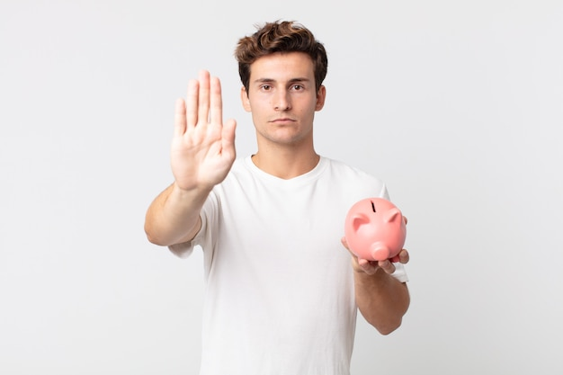 Młody przystojny mężczyzna wygląda poważnie pokazując otwartą dłoń, wykonując gest zatrzymania i trzymający skarbonkę