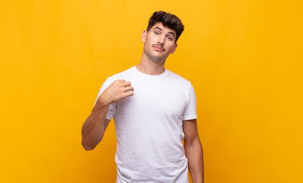 Młody przystojny mężczyzna wyglądający arogancko, odnosząc sukcesy, pozytywnie i dumnie, wskazując na siebie