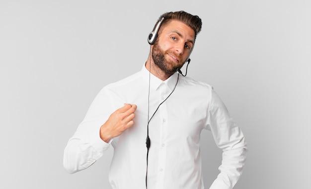 Młody przystojny mężczyzna wyglądający arogancko, odnoszący sukcesy, pozytywny i dumny. koncepcja telemarketingu