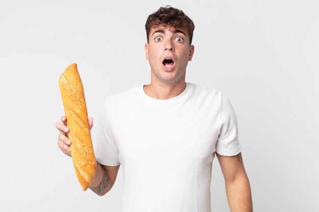 Młody przystojny mężczyzna wyglądający na bardzo zszokowanego lub zdziwionego i trzymający bagietkę z chlebem