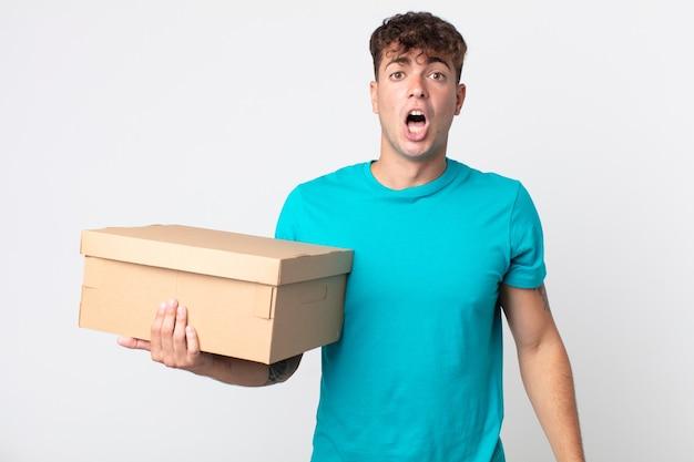 Młody przystojny mężczyzna wyglądający na bardzo zszokowanego lub zdziwionego i trzymający kartonowe pudełko