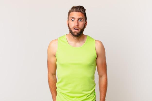 Młody przystojny mężczyzna wyglądający na bardzo zszokowanego lub zdziwionego. koncepcja fitness