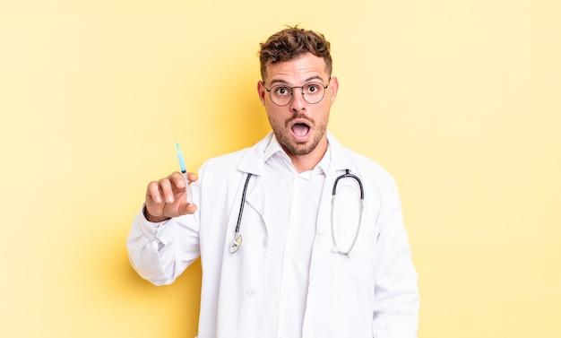 Młody przystojny mężczyzna wyglądający na bardzo zszokowanego lub zdziwionego. koncepcja strzykawki lekarza