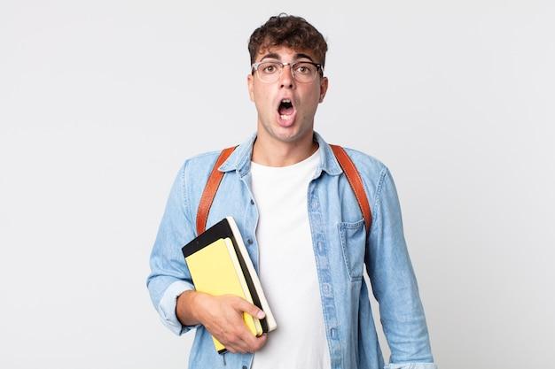 Młody przystojny mężczyzna wyglądający na bardzo zszokowany lub zaskoczony. koncepcja studenta uniwersytetu