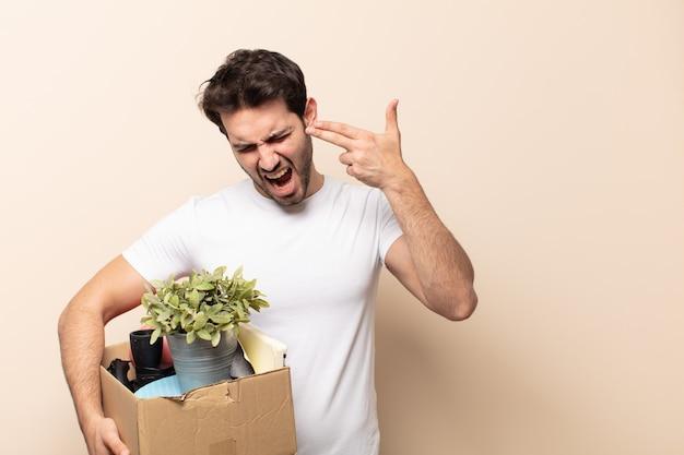 Młody przystojny mężczyzna wyglądający na nieszczęśliwego i zestresowanego, samobójczy gest, który robi znak pistoletu ręką, wskazując na głowę