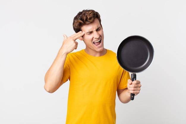 Młody przystojny mężczyzna wyglądający na niezadowolonego i zestresowanego, samobójczy gest, robiący znak pistoletu i trzymający patelnię kucharską