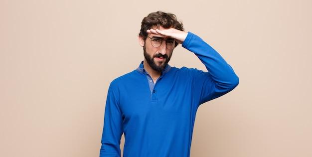 Młody przystojny mężczyzna wyglądający na oszołomionego i zdumionego, z ręką na czole, patrzący w dal, obserwujący lub szukający w płaskiej ścianie
