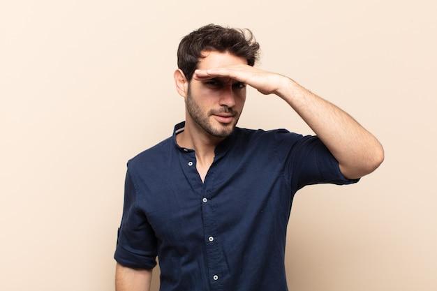 Młody przystojny mężczyzna wyglądający na oszołomionego i zdziwionego, z ręką nad czołem patrzącym w dal, obserwującym lub poszukującym