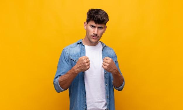 Młody przystojny mężczyzna wyglądający na pewnego siebie, wściekłego, silnego i agresywnego, z pięściami gotowymi do walki w pozycji bokserskiej