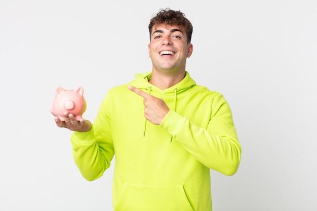 Młody przystojny mężczyzna wyglądający na podekscytowanego i zdziwionego, wskazując na bok i trzymający skarbonkę