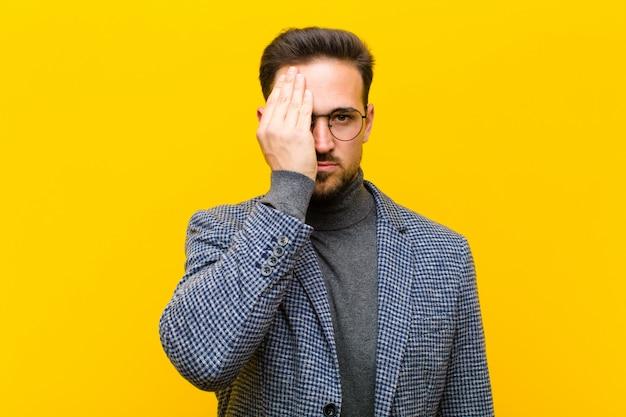 Młody przystojny mężczyzna wyglądający na sennego, znudzonego i ziewającego, z bólem głowy i jedną ręką zakrywającą połowę twarzy przed pomarańczą