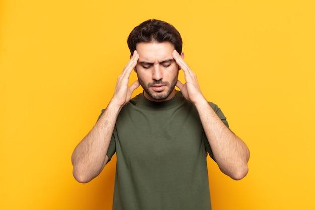 Młody przystojny mężczyzna wyglądający na skoncentrowanego, zamyślonego i natchnionego, przeprowadzający burzę mózgów i wyobrażający sobie z rękami na czole